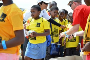 A volunteer is assisted by a teacher in handing out cup cakes. Pictures by : Thobele Nzama