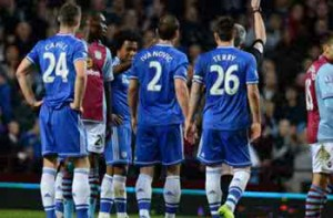 Chelsea players around the referee showing discontent at Villa Park picture from: goal.com
